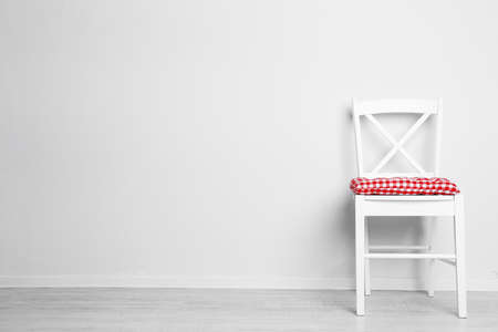 text room: Modern chair with pillow on white wall background