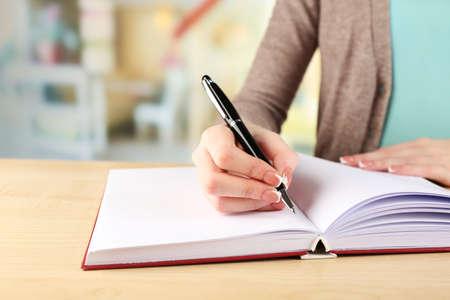 napsat: Ženská ruka s perem psaní na notebooku, detailní