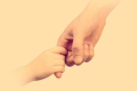 children hands: Child and mother hands together on light background