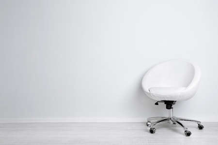 Modern chair on white wall background Foto de archivo