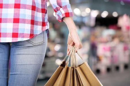 Vrouwelijke hand met winkelen papieren zakken in de markt