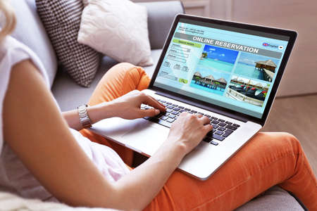 holidays: Woman using laptop to book hotel online