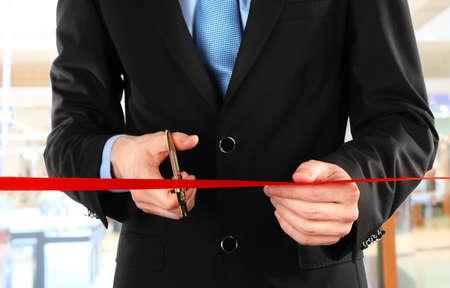 scissor cut: Businessman cutting red ribbon with pair of scissors close up