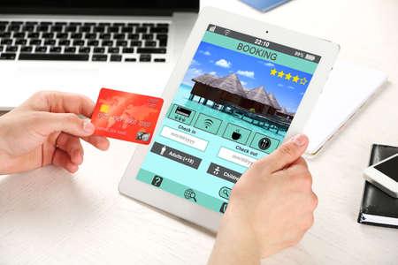 Mann hält Tablett mit Screen-Oberfläche von der Hotelbuchung Standard-Bild