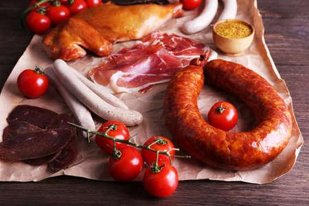 carnes y verduras: Surtido de embutidos en el pergamino en el fondo mesa de madera Foto de archivo