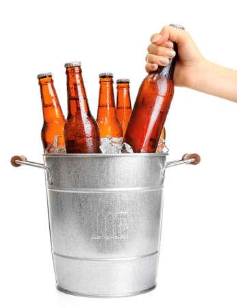 Mano femenina botella toma vaso de cerveza del cubo de metal aisladas en blanco Foto de archivo