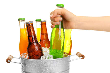 barmen: Female hand taking glass bottle of drink from metal bucket isolated on white