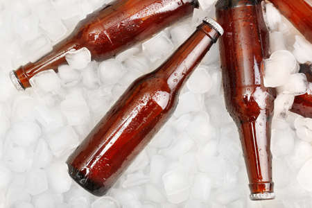 green beer: Glass bottles of beer with ice cubes, closeup