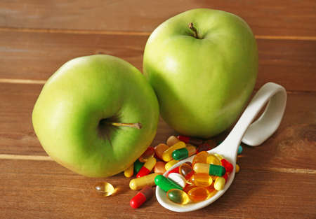 apple gmo: Apple and colorful pills, on wooden background