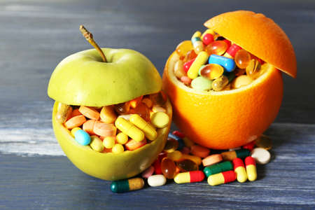 apple orange: Apple, orange and colorful pills, on color wooden background
