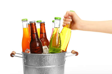 beer bucket: Female hand taking glass bottle of drink from metal bucket isolated on white