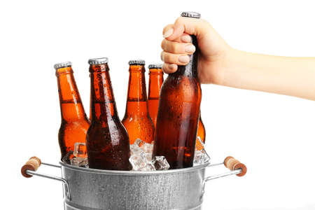 beer bucket: Female hand taking glass bottle of beer from metal bucket isolated on white