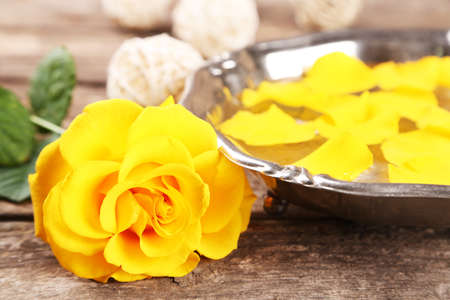 glower: Rose flower and petals in bowl on wooden background
