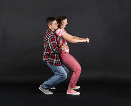 Emotional young couple on black background Imagens