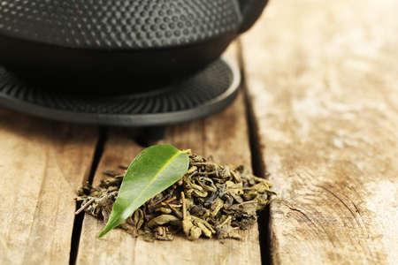 medicina tradicional china: El té verde con la hoja en la tabla de madera