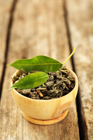 tea plant: Green tea with leaf in bowl on old wooden table Stock Photo