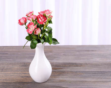 Beautiful roses in vase on table on light background Stock Photo