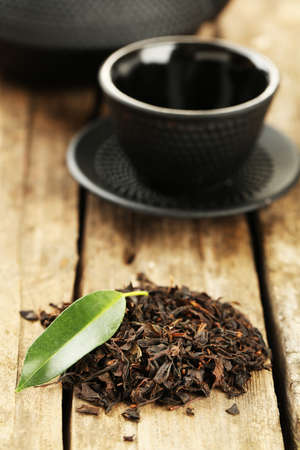 drink tea: Black tea with leaf on old wooden table Stock Photo