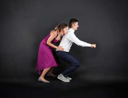 Funny young couple on black background Imagens