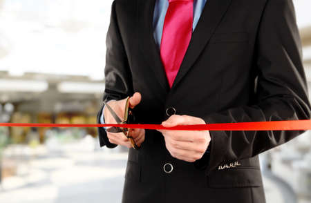 scissors cutting: Businessman cutting red ribbon with pair of scissors close up