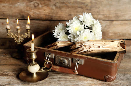 retro flowers: Old wooden suitcase with old books and flowers on wooden background