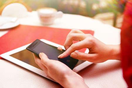 cafe internet: Mujer con el tel�fono m�vil y el ordenador tableta en la tienda de caf� Foto de archivo