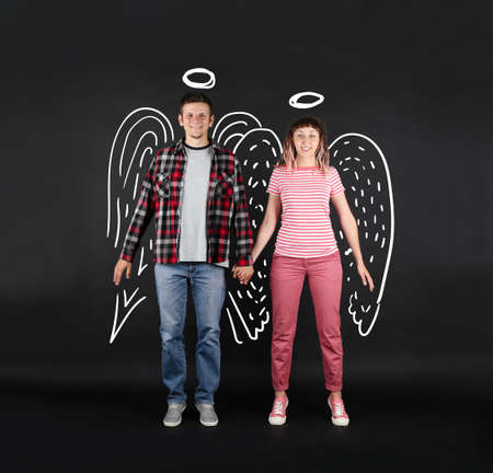 Funny young couple as angels , on black background