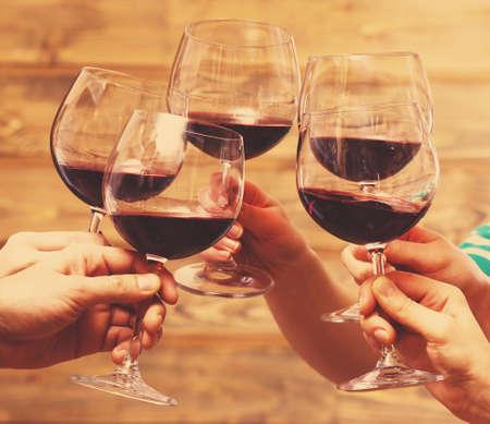 Tintinean los vidrios de vino rojo en las manos sobre fondo de madera rústico tablones