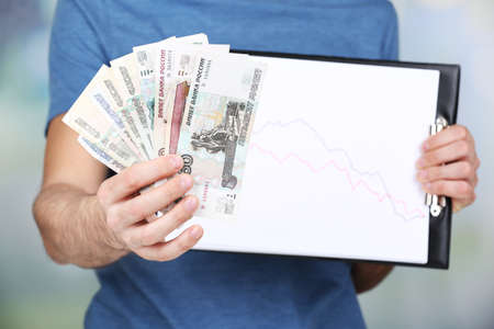 man holding money: Man holding money and graph document close up