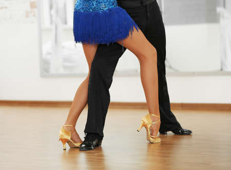 masculine: Beautiful womanish and masculine legs in active ballroom dance, indoors