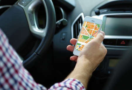 road trip: Man sitting in the car and holding smart phone with map gps navigation application