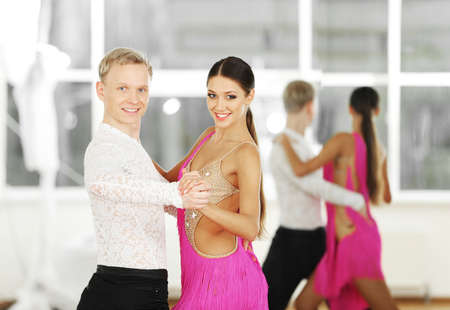 Beautiful couple in active ballroom dance, indoors