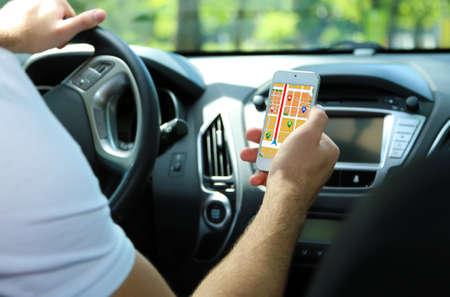 to navigation: Hombre sentado en el coche y la celebraci�n de tel�fono inteligente con aplicaci�n de navegaci�n gps mapa Foto de archivo