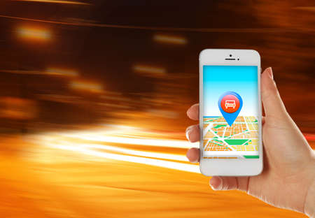 taxi: Hand holding mobile smart phone with interface taxi on night background Stock Photo