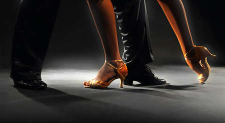 latin couple: Feet partners on black background Stock Photo