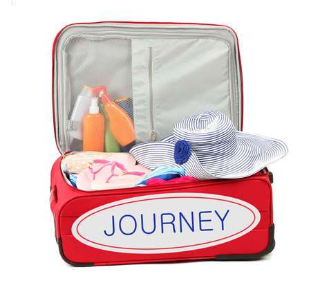 opened bag: Journey concept. Suitcase with summer clothes, hat and suntan isolated on white Stock Photo