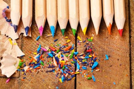 sharpening: Wooden colorful pencils with sharpening shavings, on wooden table