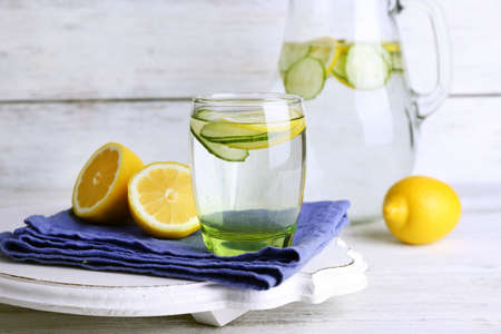 lemon water: Fresh water with lemon and cucumber in glassware on wooden background