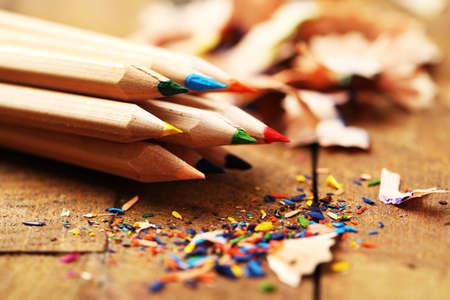 木製テーブルの上の削りくずをシャープで木製のカラフルな鉛筆