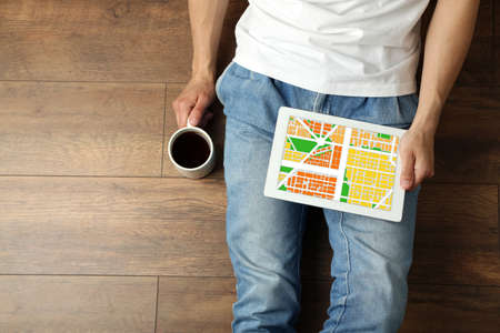 cartography: Young man sitting on floor and holding tablet with map gps navigation application