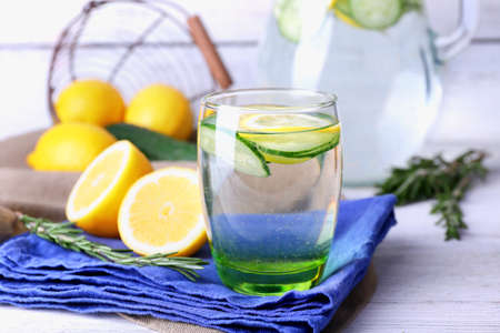 limón: Fresh water with lemon and cucumber in glassware on napkin on wooden table, closeup
