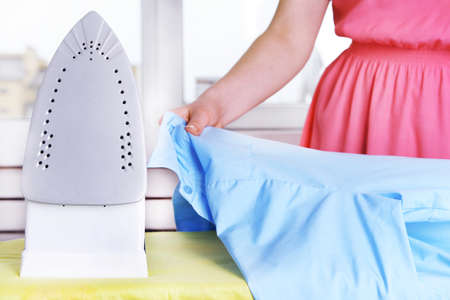 steam iron: Woman ironing clothes on ironing board, closeup Stock Photo