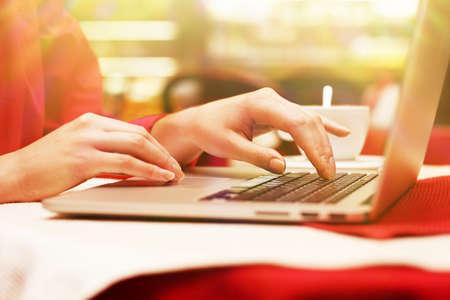 obra social: Mujer con ordenador portátil en la tienda de café