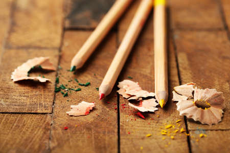 sharpening: Wooden colorful pencils with sharpening shavings on wooden table