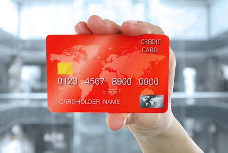 cash slips: Hand holding credit card on abstract background Stock Photo
