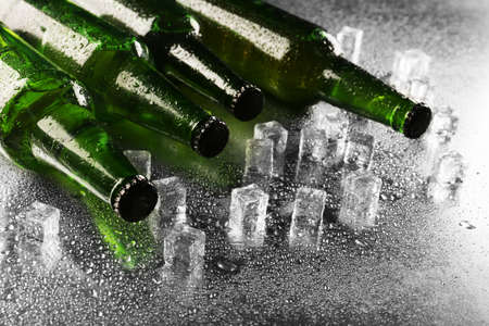 beer bottle: Glass bottles of beer with ice cubes on wet table background