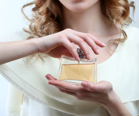 Mooie jonge vrouw met parfumfles isoleren op wit