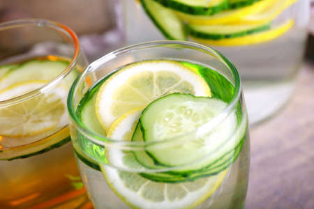 lemon slices: Fresh water with lemon and cucumber in glassware in wooden tray, closeup Stock Photo