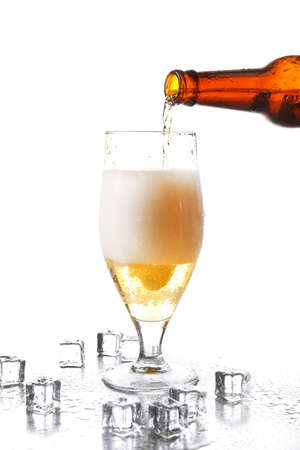 pouring beer: Pouring beer from bottle into glass isolated on white Stock Photo
