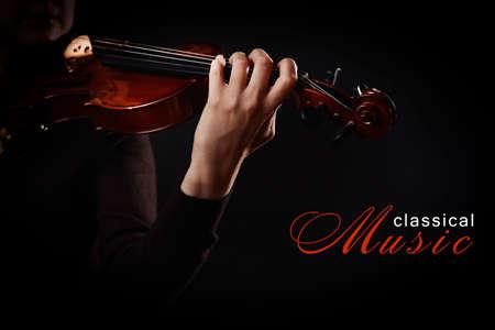 violinista: Violinista que toca el violín sobre fondo oscuro